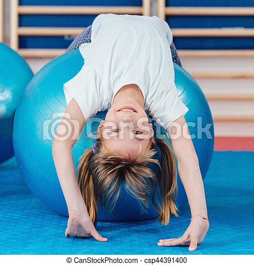 Little girl at physical education class in school gymnasium, stretching over fitness ball