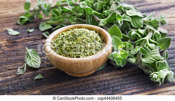 Fresh and dried oregano herb on wooden background