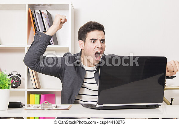 young man celebrating enthusiastically in front of laptop computer