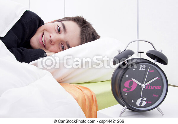 alarm clock in the foreground of the room with the child sleeping in bed