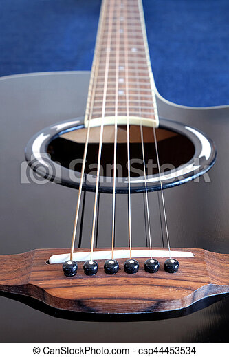 Classic acoustic six strings guitar black color with long neck top with cutaway fragment on jeans background side view closeup