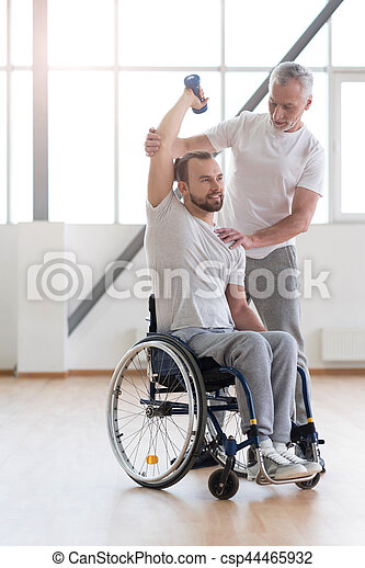 On my way to the healthy life. Athletic confident cheerful disabled man holding the dumbbell and having the lesson with his coach while having the physical therapy session in the gym