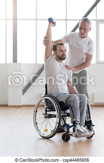My healthy lifestyle. Athletic strong handsome disabled man in the wheelchair holding the dumbbell and having the lesson with his coach while having the physical therapy session in the gym