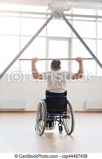 Overcoming my laziness . Athletic skillful young disabled man sitting in the wheelchair in the gym and looking at the window while exercising and holding the metal barbell