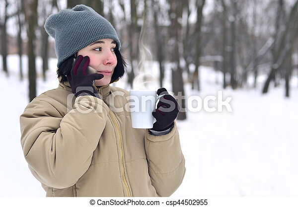 Pretty young girl wear warm winter hat and coat. Fun brunette female model walk outside with smartphone and coffee cup in cold weather. Smiling happy model posing. Good holiday weather