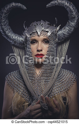 Warrior, Viking goddess, beautiful young blond woman with horned helmet made of iron. Fantasy image and stories
