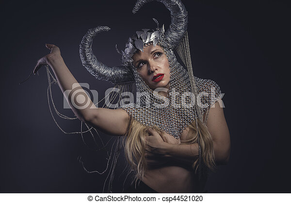 Sexy Viking goddess, beautiful young blond woman with horned helmet made of iron. Fantasy image and stories