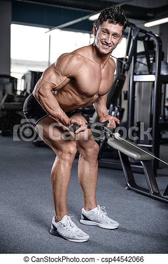 Handsome bodybuilder training in the gym sexy man lift dumbbells with topless body strong abs healthcare lifestyle