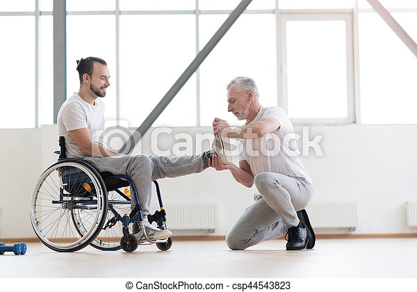 Doing my job professionally. Proficient athletic aged orthopedist helping the disabled man and providing a rehabilitation session while expressing concentration