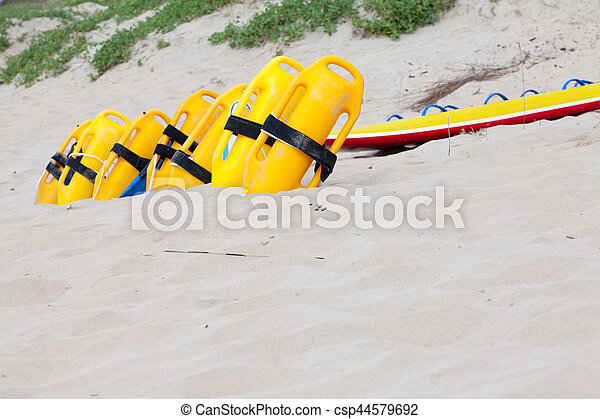 Row of bright yellow floatation devices on beach - csp44579692
