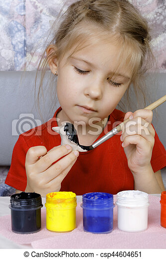 Girl paints her crafts (focus on brush)