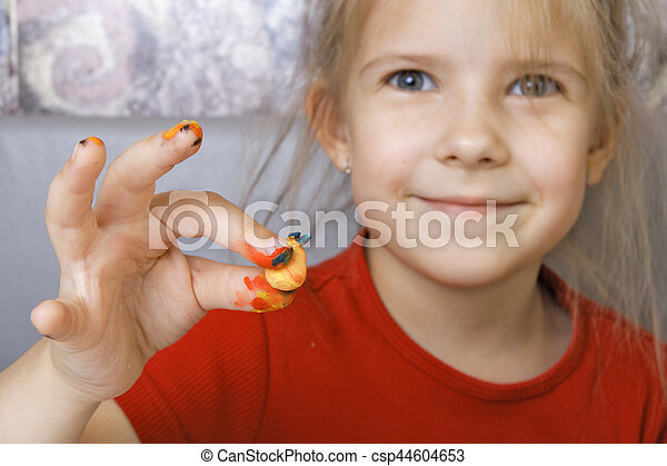 Girl shows a homemade painted crafts (focus on the hand)