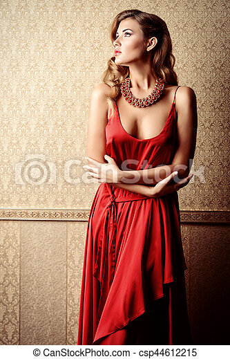 Beautiful charming woman wearing evening red dress and a necklace of gems posing over luxurious vintage background. Beauty, fashion. Evening make-up and hairstyle. Jewellery.