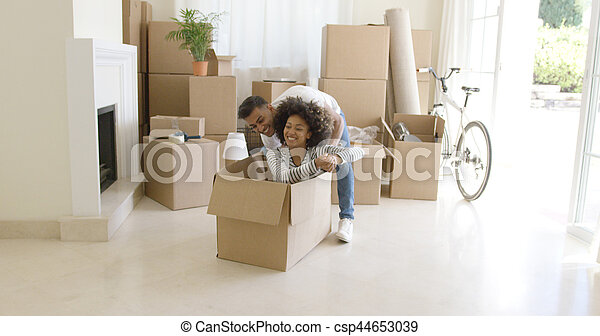 Fun young African woman with an afro hairstyle sitting inside a packing box with her laughing husband behind her as they move into a new home with a stack of packed cartons.