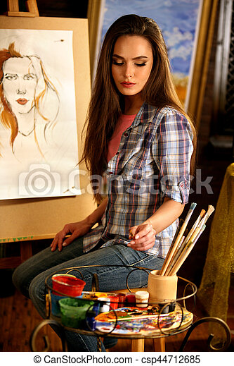 Artist painting on easel in studio. Girl paints portrait of woman with brush. Female painter seen from behind. She thinks about choice of brushes. Indoor home interior for handmade crafts.