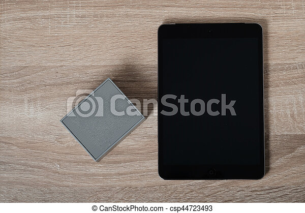 Top view wireless portable speaker connect to blank screen mobile device on a wooden table