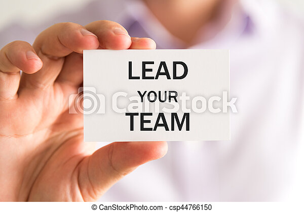 Closeup on businessman holding a card with text LEAD YOUR TEAM, business concept image with soft focus background