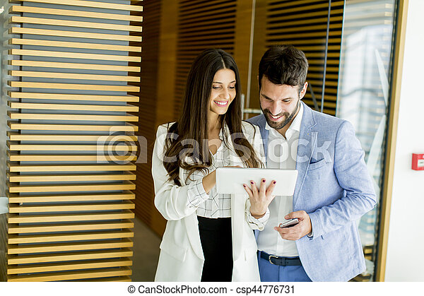 Business colleagues working and holding a digital tablet in modern office