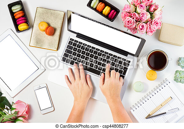 Feminine workspace with laptop, tablet and phone with someones hands, top view