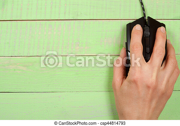 black computer mouse with a hand on a green wooden background with copy space for your text. Top view.