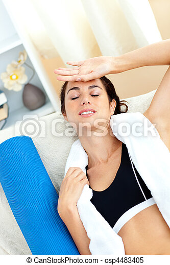 Tired woman sitting on a sofa after working out in her living-room at home - csp4483405