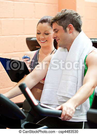 Handsome male athlete exercising on a bicycle with his personal coach in a fitness center - csp4483530