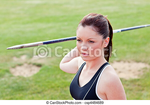Determined female athlete ready to throw javelin - csp4484689