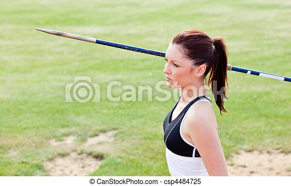 Concentrated female athlete ready to throw javelin - csp4484725