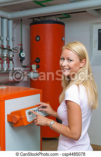 Woman in the boiler room for heating. Save energy - csp4485078