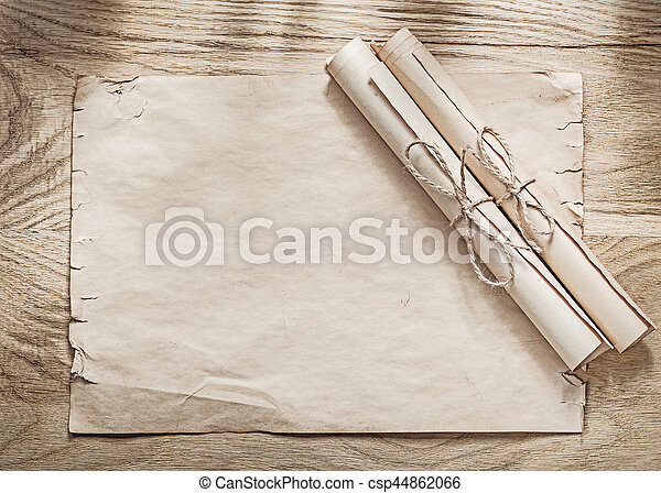Medieval parchment paper rolls on wooden board.