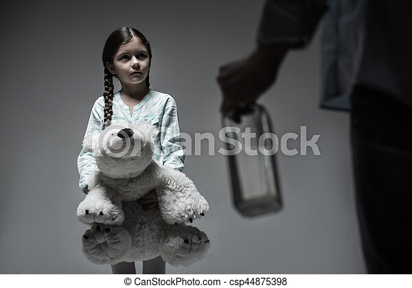 One more time. Scared sad girl with widely opened eyes looking straight at male person with bottle in hand while hugging big bear toy standing over grey background
