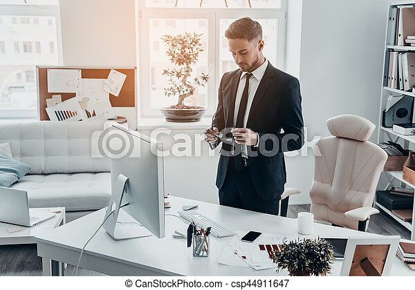 Preparing to work hard. Good looking young man in full suit holding eyeglasses while standing in the office