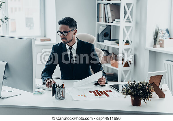 Busy at work. Handsome young man in full suit working with documents while sitting at the office desk
