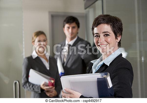 Three office workers at door of boardroom - csp4492917