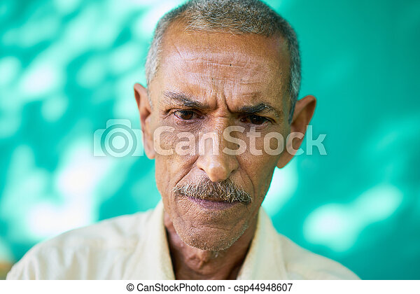 Real Cuban people and emotions, portrait of sad old latino man from Havana, Cuba looking down with worried face and depressed expression