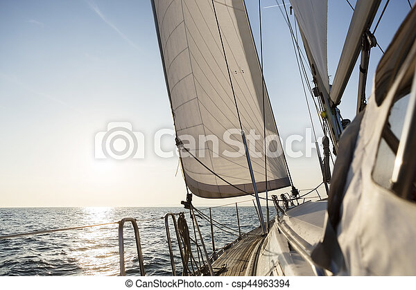 Luxury sail boat sailing in open sea against sky during sunrise