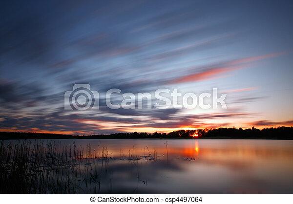 Blue cold sunrise over lake