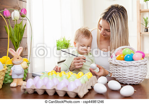 Easter concept. Happy mother and her cute child getting ready for Easter - csp44981246