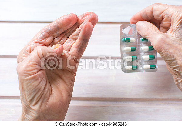 Senior woman hands taking out pill - csp44985246
