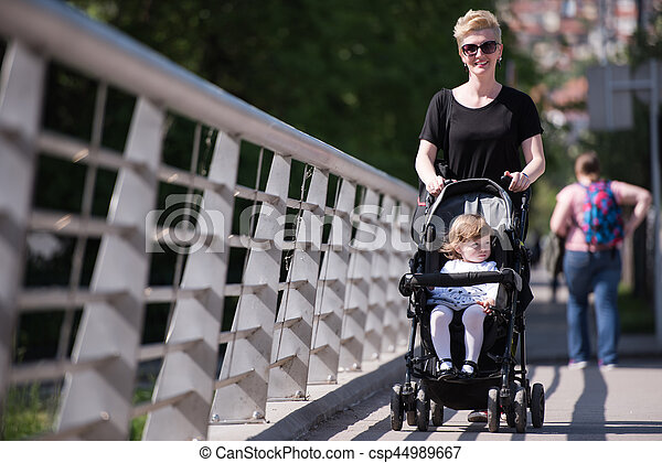 mother pushed her baby daughter in a stroller - csp44989667