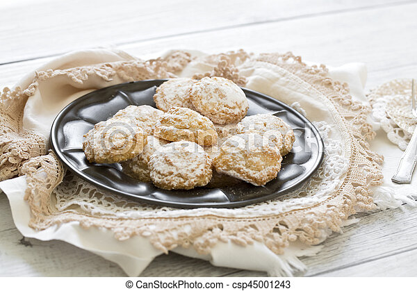 Coconut biscuits with icing sugar over pewter plate - csp45001243