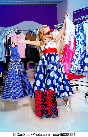 Little fashion-monger girl wearing beautiful pin-up dress and sunglasses goes shopping. Children\'s fashion. Sale and shopping concept.