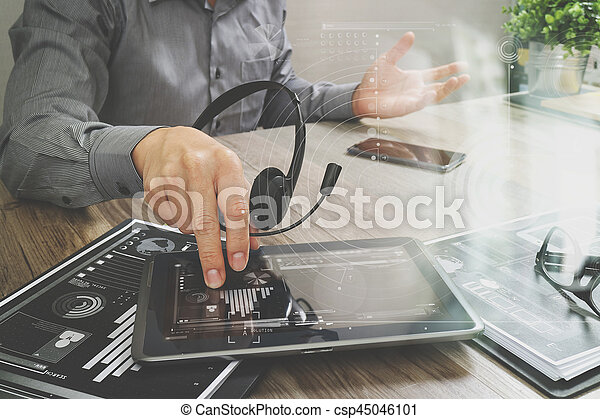 Businessman hand using VOIP headset with digital tablet computer,document,concept communication,icon graph interface, call center and customer service help desk