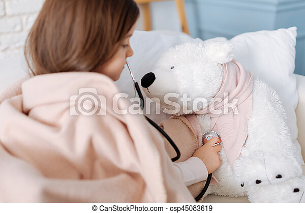 Are youhealthy. Pleasant cute little girl sitting on the couch and holding stethoscope while curing her fluffy toy