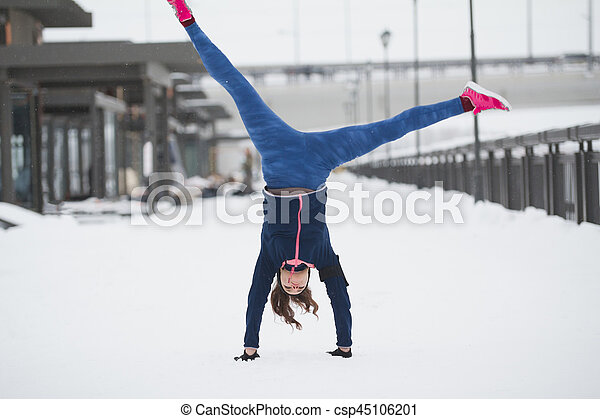 Fitness girl have acrobatic work out fitness at snow winter promenade, sport background, telephoto