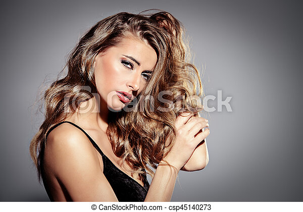 Portrait of a beautiful young woman with dark make-up and wavy hair. Femininity. Sexual woman. Beauty, fashion and cosmetics concept.