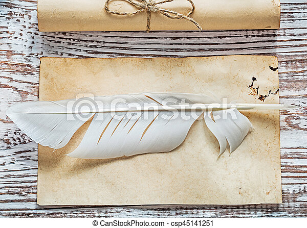 Medieval parchment corded paper rolls quill on vintage wood board.