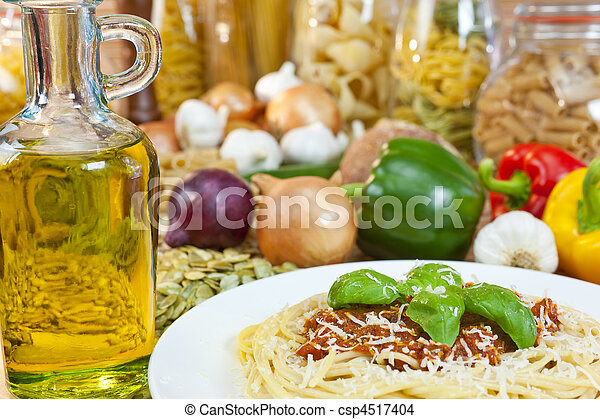 Spaghetti Bolognese with olive oil, Parmesan cheese, basil garnish various Italian pasta and ingredients out of focus in the background. - csp4517404