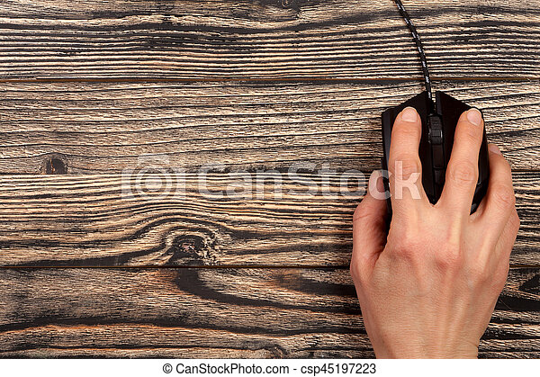 black computer mouse with a hand on a black wooden background with copy space for your text. Top view.