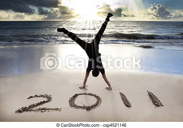 happy new year 2011 on the beach of sunrise . young man handstand and celebrate . - csp4521146